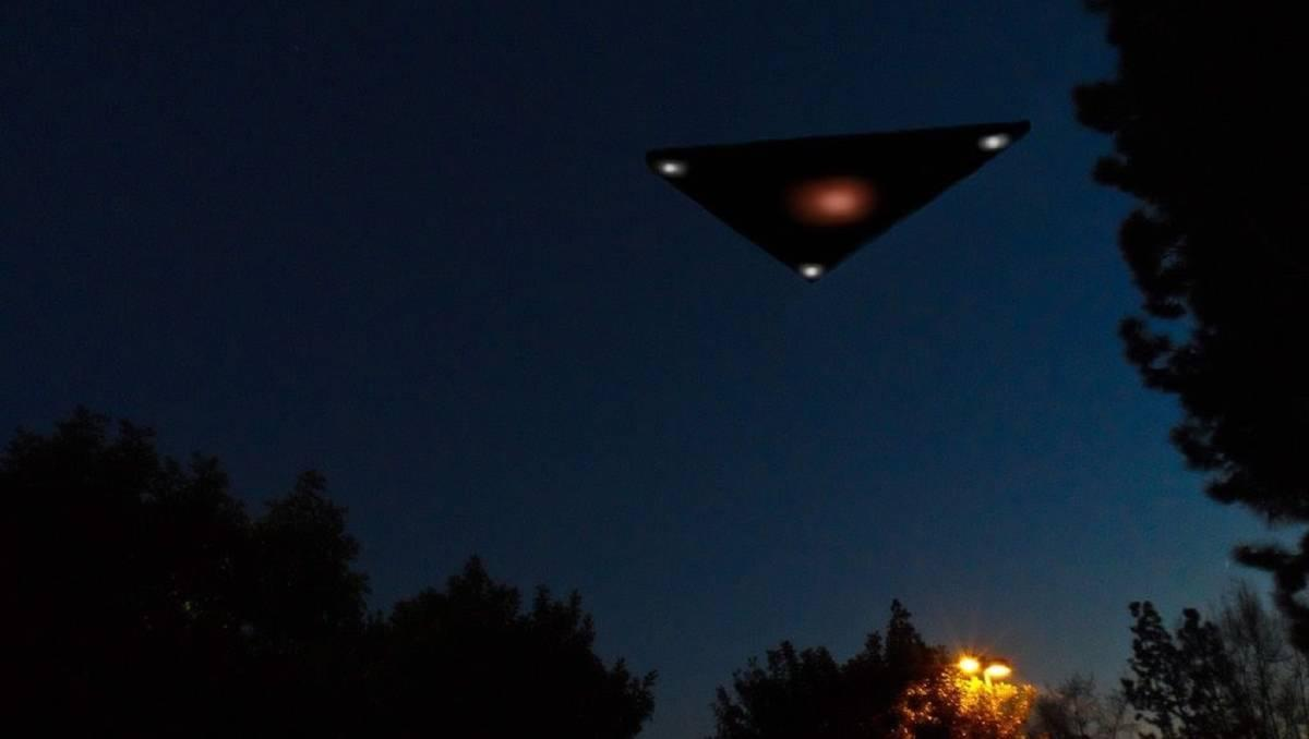 An illustration of a black triangle UFO flying over the treetops at night.