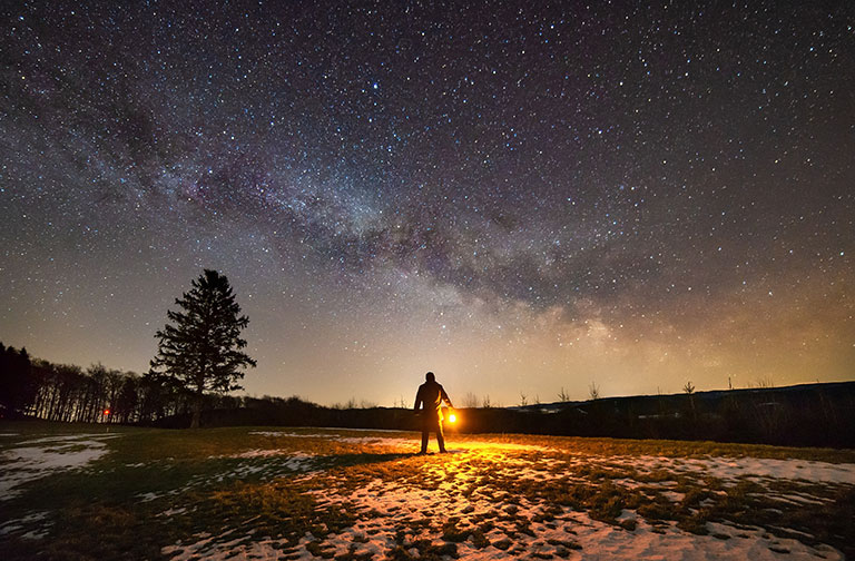 Figure holding a lantern with Milky Way galaxy in background.