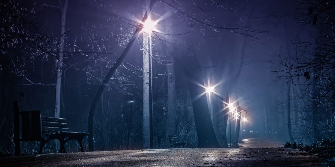 Park lights illuminate the sidewalk on a dark night.