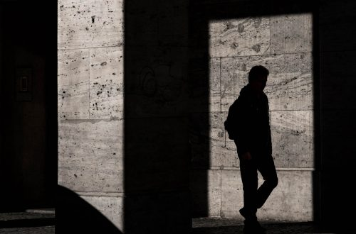 Silhouette on the wall of a man walking.