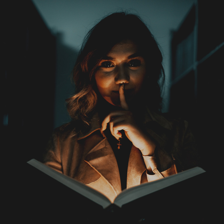 Woman making a hush expression while opening a book.