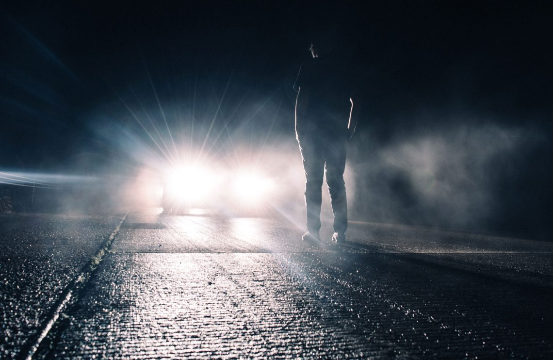 Man standing in front of car headlights.