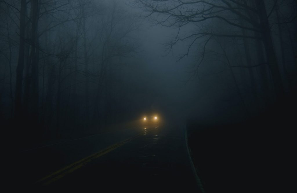 Vehicle headlights are visible on a dark road.