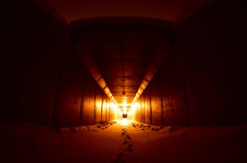 Long dark corridor with light at the end of the tunnel.