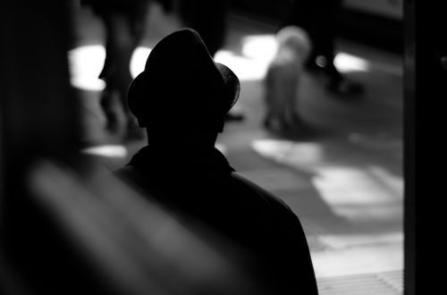 Silhouette of man standing in the train station watching people.