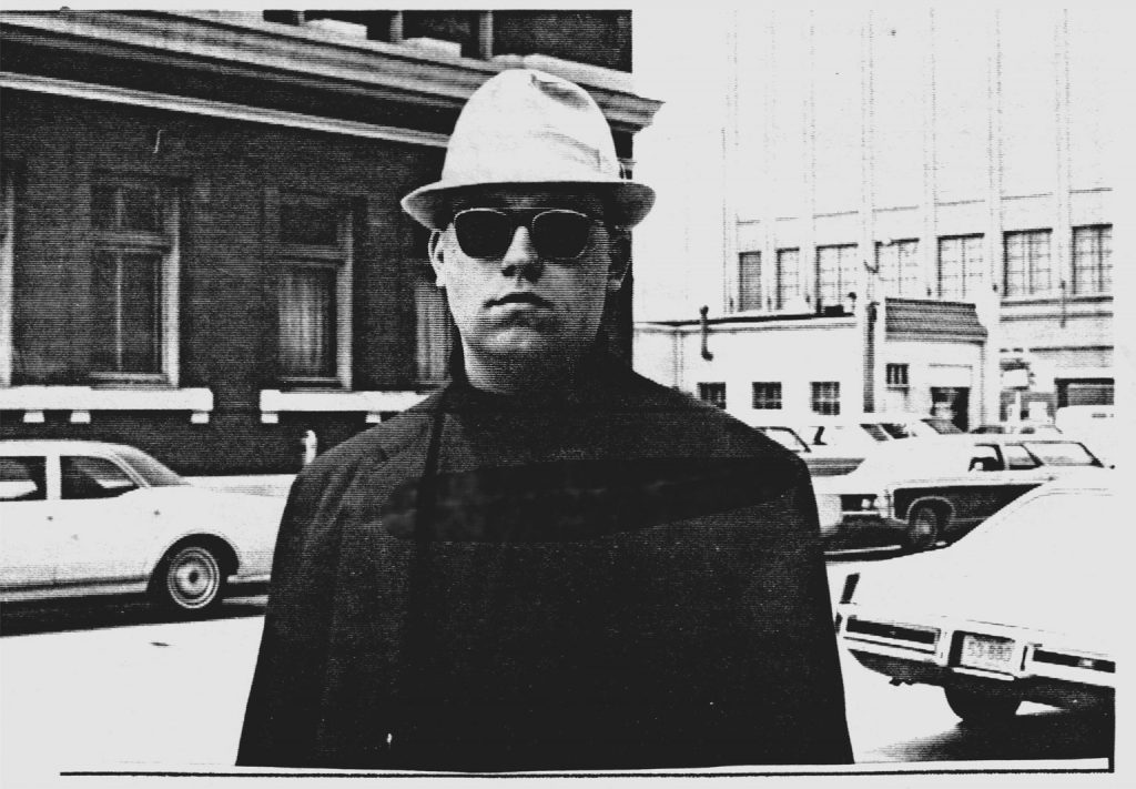 Photo of a man in black attire with a white fedora hat and dark sunglasses staring at the camera.
