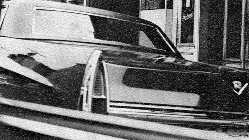 The rear of a black Cadillac.
