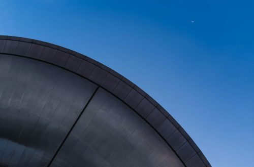 A domed structure with the moon high up in the sky.