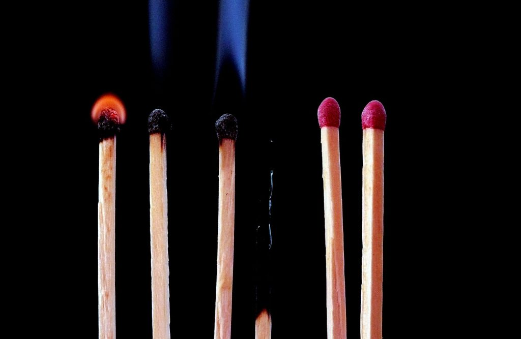 Six burning matches with two unlit.