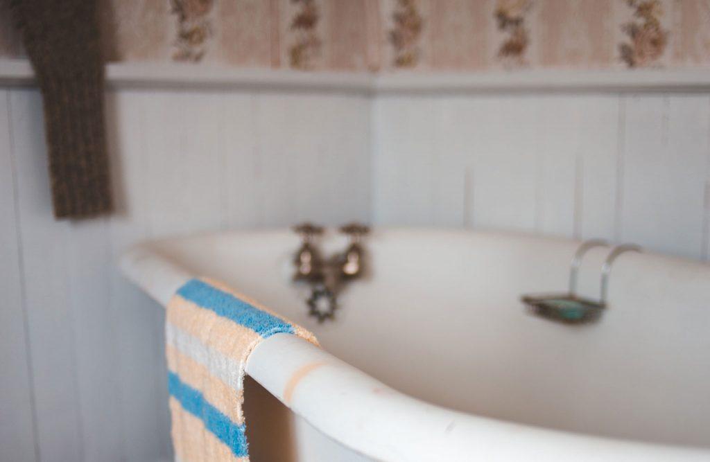 An empty vintage style bathtub in a bathroom.