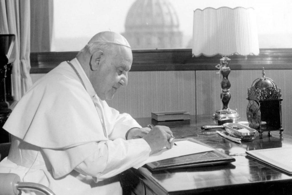 Pope John XXIII at desk writing.